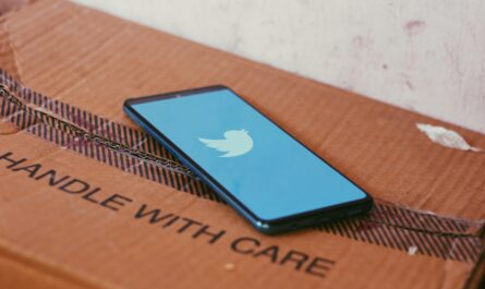 Twitter app on an iPhone that is resting on a cardboard box that reads handle with care